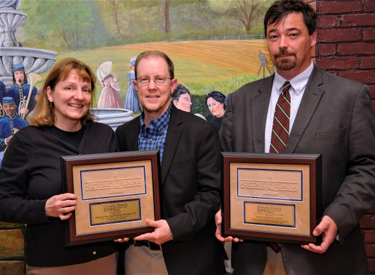 Susi Brady-Adams and Seth Adams, left, owners of Warner's Way Real Property Services, and David Anderson of Johnson-Schmidt & Associates show off plaques for this year's Preservation Awards presented by Historic Elmira Inc.