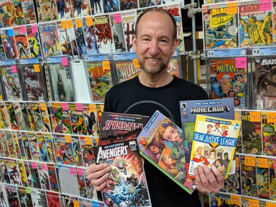 Chris Rupp, owner of Rupp's Comics, holds some of the comics that will given away for free Saturday.