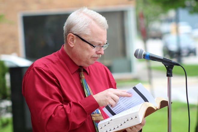 Saint Joseph Catholic Church Deacon Mell Schell prays over media members during National Day of Prayer Thursday.