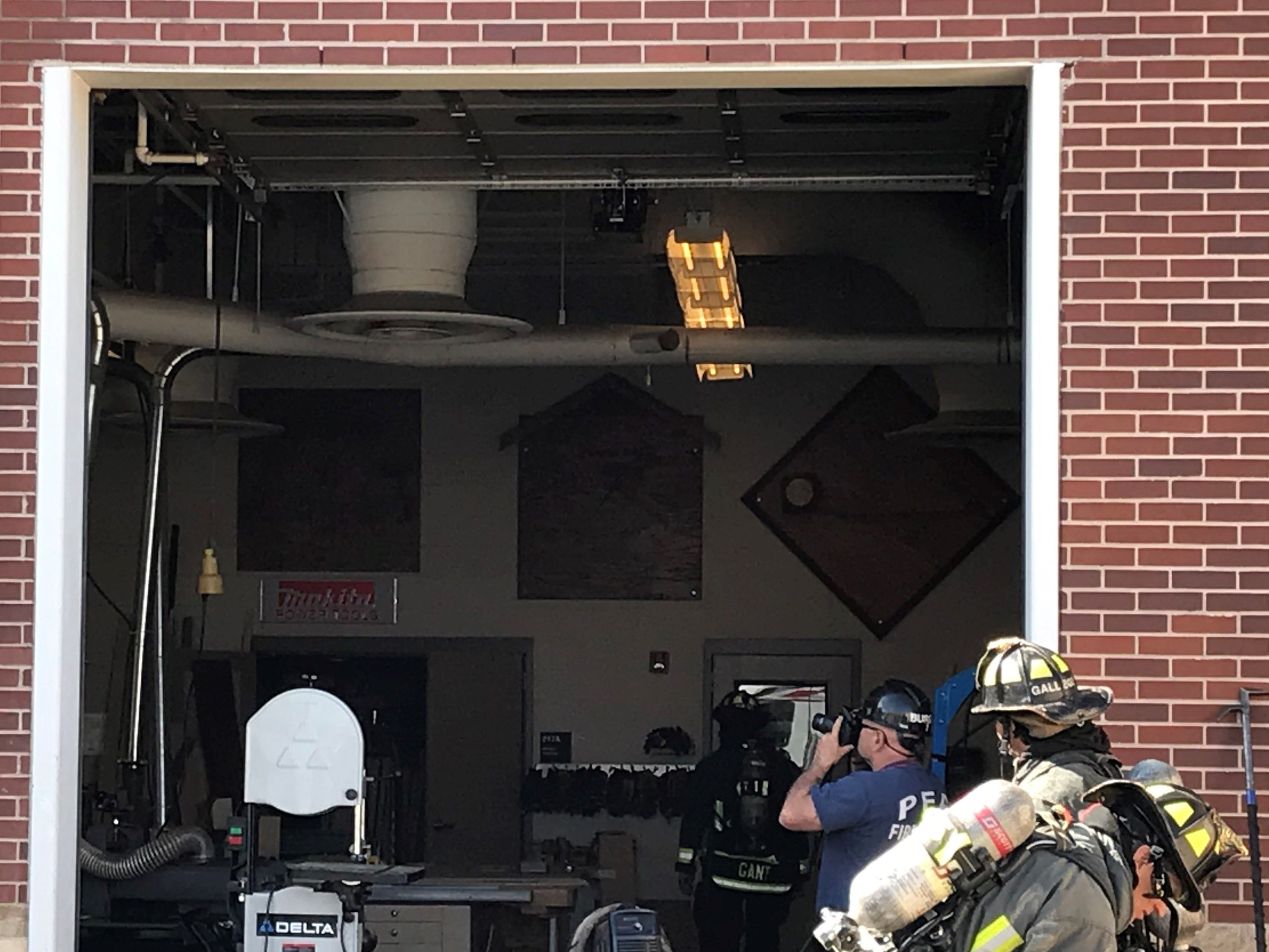 A Poudre Fire Authority investigator takes photos of the inside of the industrial arts building at Fossil Ridge High School, where a fire broke out Thursday morning.