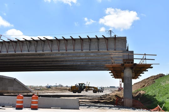 A grader levels the road Thursday where Interstate 25 will run under a new bridge being built at Colorado Highway 402.