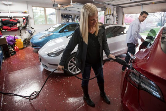 Nichole Camp demonstrates the charging procedure of her red 2018 Tesla Model 3 while her husband Dan closes the door while in their garage with Dan's Model 3 and their son, Branson's, Nissan Leaf on Wednesday, May 1, 2019, at their home in Fort Collins, Colo.