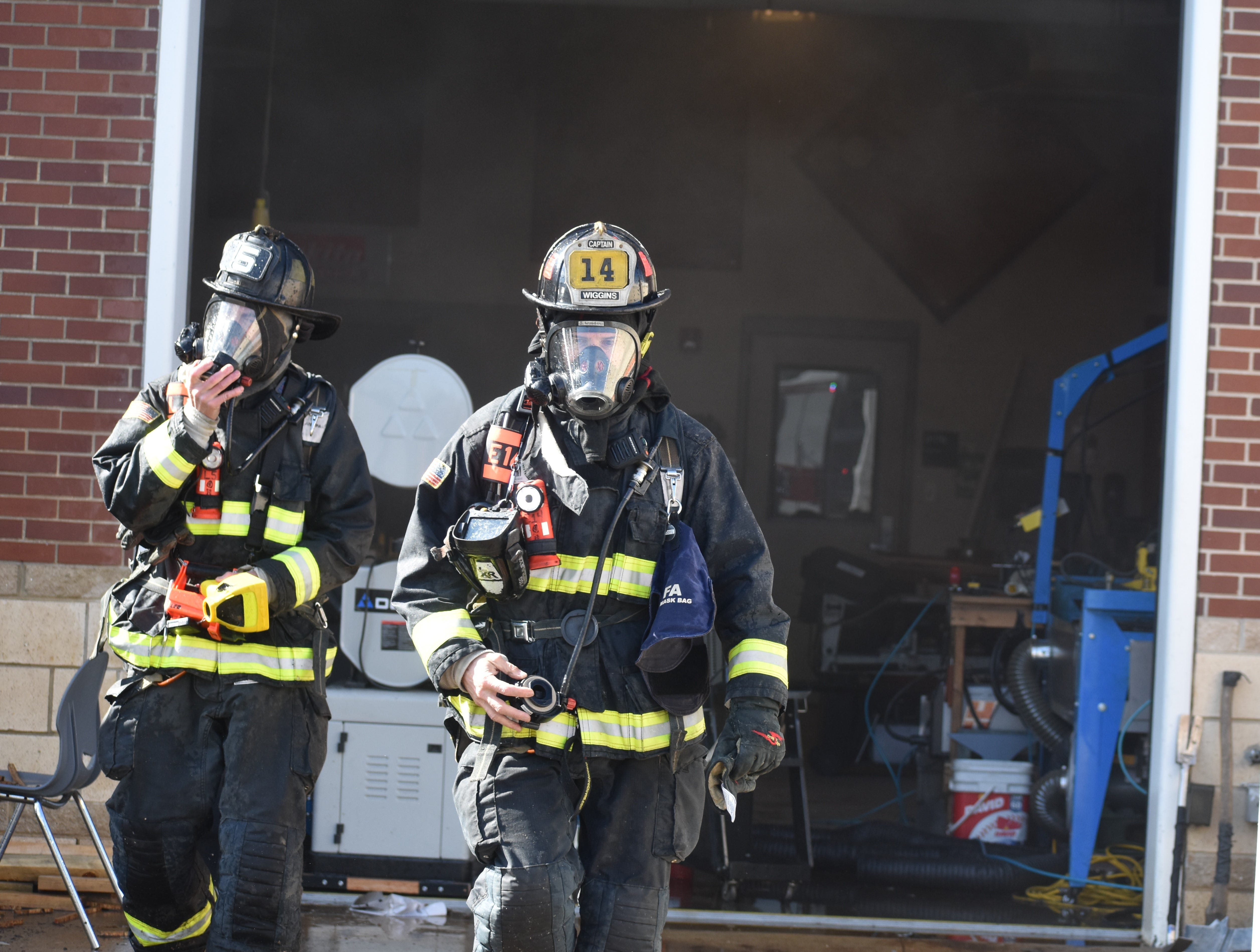 Poudre Fire Authority firefighters emerge from the fire in the industrial arts building at Fossil Ridge High School on Thursday.