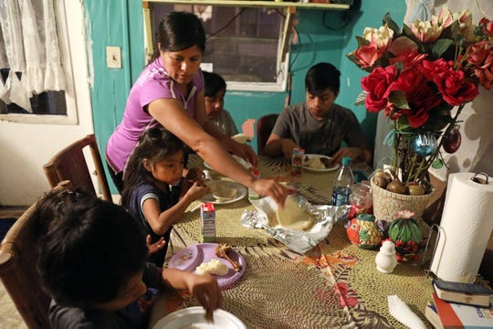 Bernabela Gonzalez serves freshly made tortillas for dinner in the trailer she and her husband rent in Immokalee on Wednesday evening.