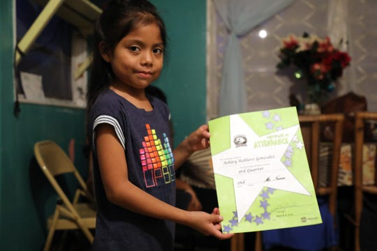 Ashely Gonzalez shows an attendance award she earned in school in Immokalee. Although she and her siblings live in crowded trailer conditions with no private space to study, she's doing well in school.