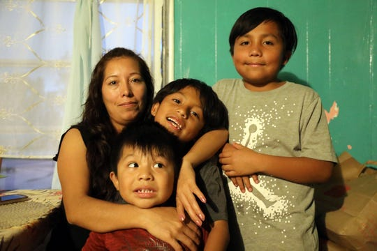Amalia Mejia poses with her three children for a portrait in the trailer where she lived with her in-laws' family and two other adults after Hurricane Irma . The house they previously rented was severed by a falling tree during the hurricane, and irreparably damaged. Another Mejia lived in, owned by a former employer, allowed supervisors to come and go freely, including one who tried to force himself on her.