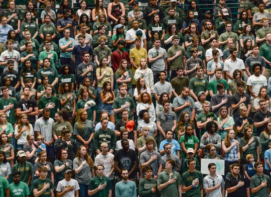 Students join sing the national anthem during vigil Wednesday night at the University of North Charlotte. (Ken Ruinard/ Independent Mail / USAToday / 2019)