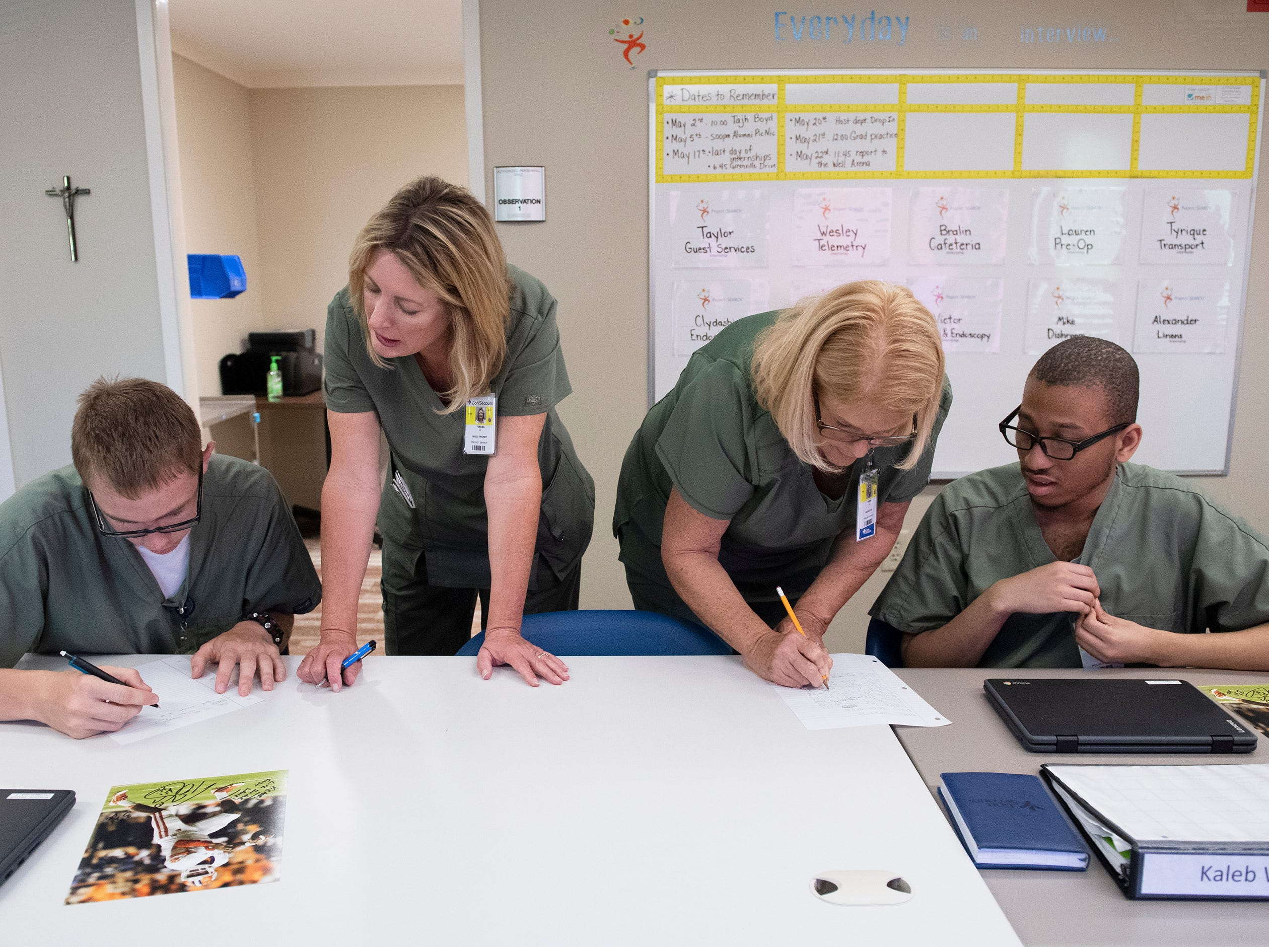 Project SEARCH skills trainer Teresa Gibson (second from left) and support instructor Marie Miller work with students Victor Cantrell (left) and Kaleb Watkins (right) in class Thursday, May 2, 2019.