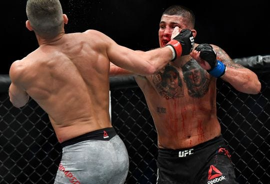 "A bloodied Anthony Pettis, right, delivers a knockout punch to Simpsonville's Stephen ""Wonderboy"" Thompson in Nashville, Tenn., on March 23."
