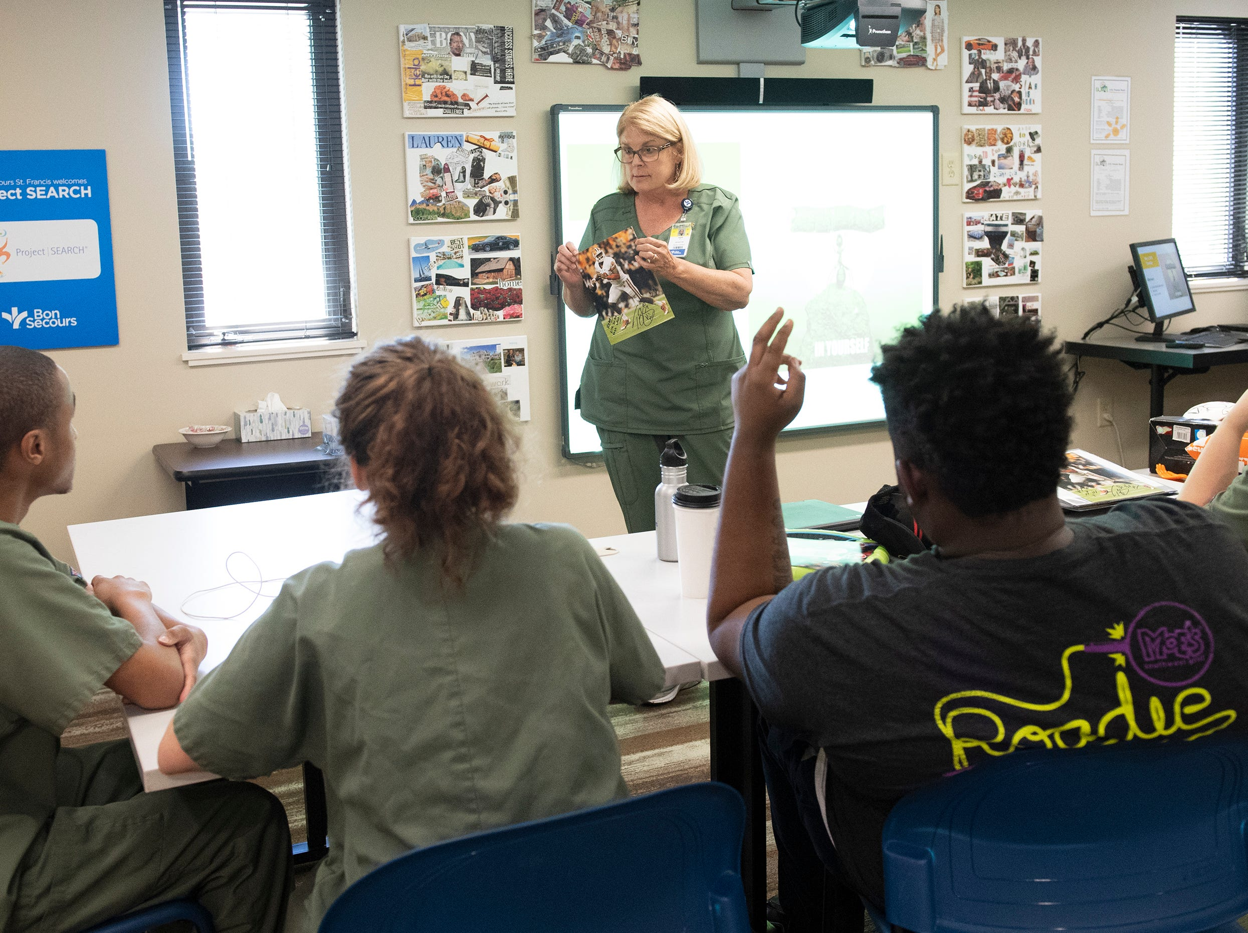 Marie Miller, a support instructor with Project SEARCH, talks to students about their visit from Tajh Boyd Thursday, May 2, 2019.