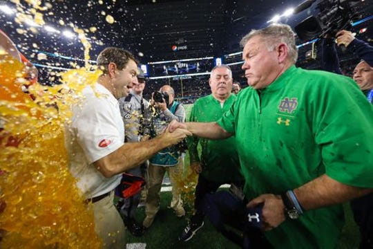 Clemson Coach Dabo Swinney, left,  gets soaked whole shaking hands with Notre Dame Coach Brian Kelly following the Cotton Bowl last December.