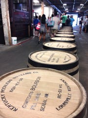 A tour group makes its way past a row of bourbon barrels at the Kentucky Peerless distillery in Downtown Louisville. The first Peerless bourbon in more than 100 years will be released in June.
