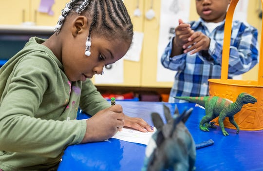 Prius Winters, 4, a pre-kindergarten student at Avondale Meadows YMCA Early Learning Center, draws a picture of her favorite dinosaur during a lesson on Tuesday, April 30, 2019.