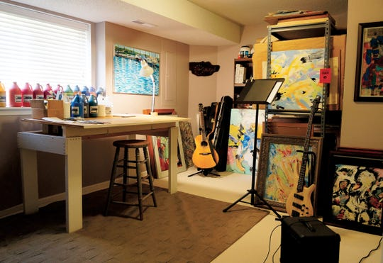 The professional studio in the Coralville home of Don Hetzel is neater than that of most artists. As you can see, guitars are his diversion and often the subjects of his work.