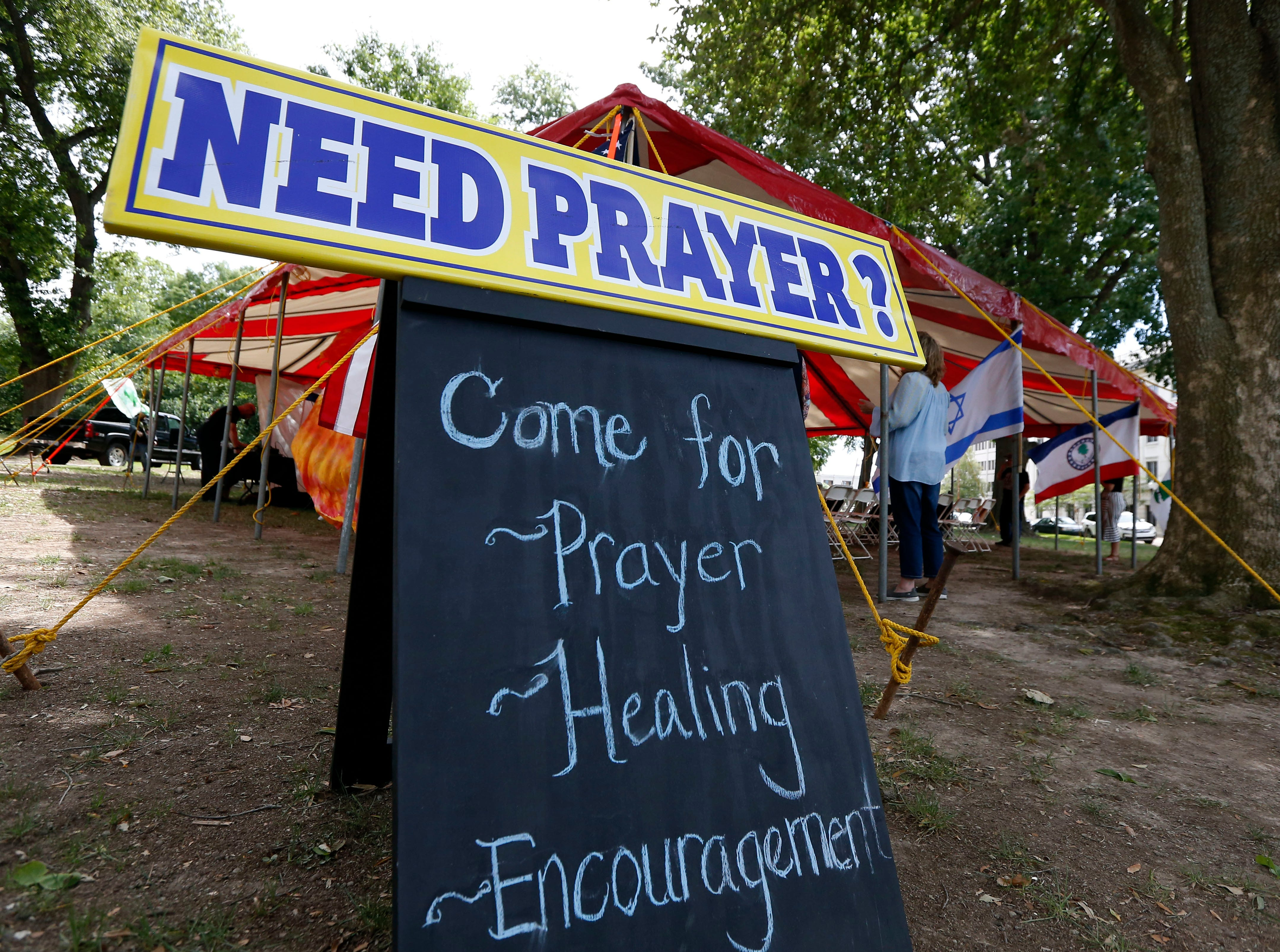 A worshiper enters a prayer tent on the grounds of the state Capitol in Jackson, Miss., Thursday, May 2, 2019, during the National Day of Prayer. The annual day of observance is held on the first Thursday of May, designated by the United States Congress, and calling on people of faith to pray for the nation and its leaders. (AP Photo/Rogelio V. Solis)