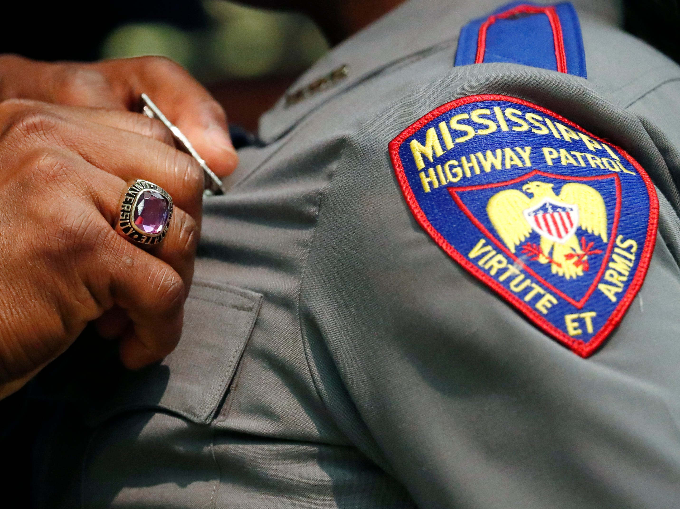Mississippi Highway Patrol director Col. Chris Gillard, left, pins the badge on the shirt of one of the 44 cadets sworn in as the newest Mississippi Highway Patrol troopers, Wednesday, May 1, 2019, at the Clyde Muse Center in Pearl, Miss.