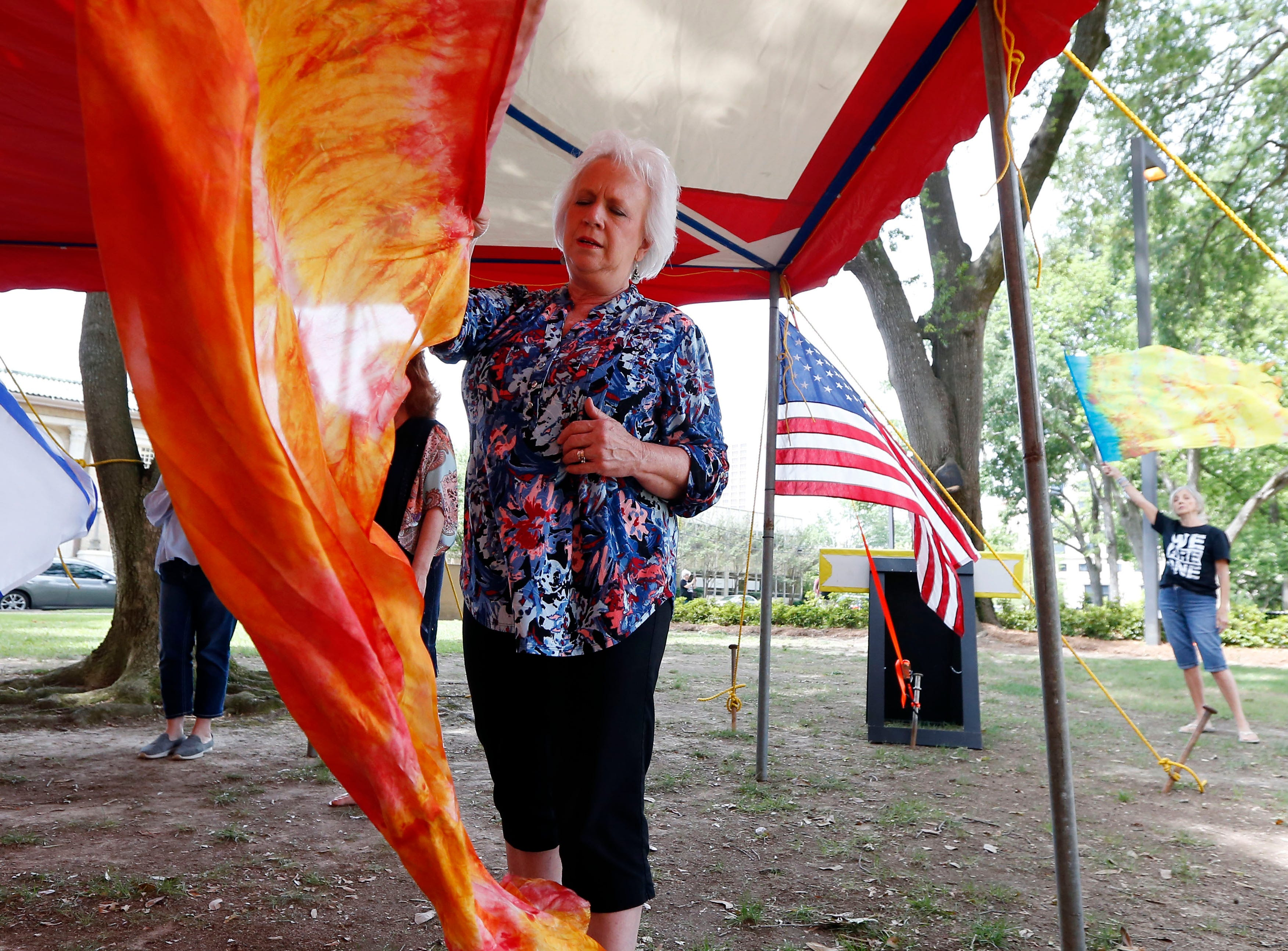 A worshiper prays as she waves a banner on the grounds of the state Capitol in Jackson, Miss., Thursday, May 2, 2019, during the National Day of Prayer. The annual day of observance is held on the first Thursday of May, designated by the United States Congress, calling on all people of faith to pray for the nation and its leaders.