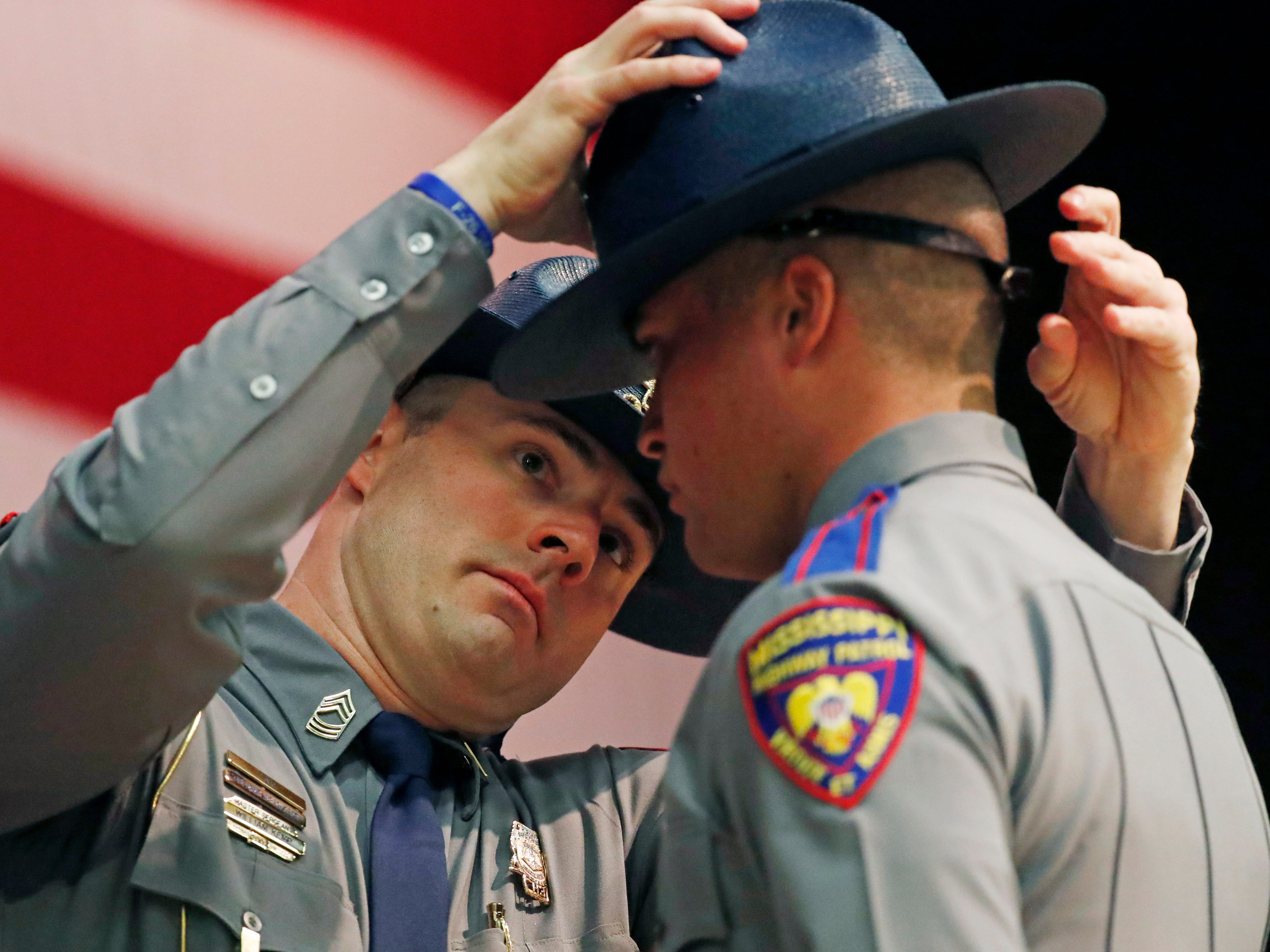 """Master Sgt. William Kemp, left, adjusts the """"cover"""" of one of the Mississippi Highway Safety Patrol Cadet Class 63 members, Wednesday, May 1, 2019, during their graduation ceremony at the Clyde Muse Center in Pearl, Miss. The patrol's training lasts 22 weeks and involves classroom instruction, physical fitness, firearms and emergency operations training as well as a variety of police science courses."""