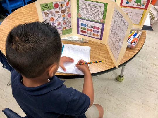 """A student in Kim Bourgeois' kindergarten ESL class at Broadmoor Elementary School in Lafayette works on a writing assignment related to the book """"The Tiny Seed."""""""