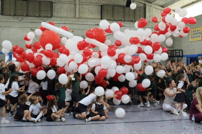 Sts. Leo-Seton Catholic School was the top earner in Community's Cash for Schools program for the second year in a row and earned the most funds for a single school in the history of the program. Students celebrate with red and white balloons Wednesday.