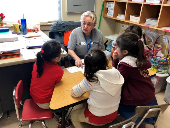 Four students work with paraprofessional Zorada Carrero at a corner desk in a first-grade ESL classroom in Lafayette.