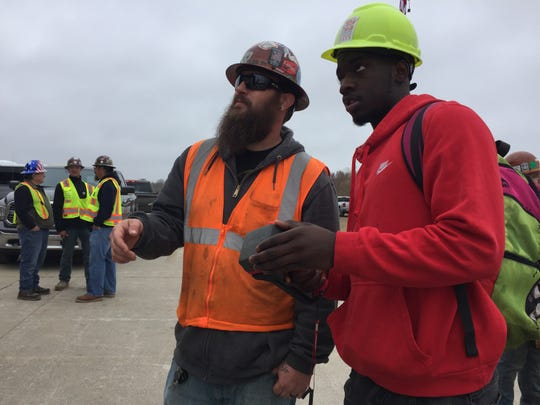 Julius Draughan, a Detroit Osborn High School junior, successfully operates a small crane by remote control, getting advice from Operating Engineers 324 crane operator Ben Malone at Construction Career Days, Thursday, May 2, 2019.