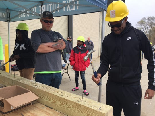 Jordan Crawford, a junior at Ferndale High School, tries his hand at carpentry, Thursday, May 2, 2019, at Construction Career Days at the Operation Engineers 342 Construction Career Center in Howell Township. Carpenter Dakota Hazel with the Michigan Regional Council of Carpenters and Millwrights Local 687 looks on.