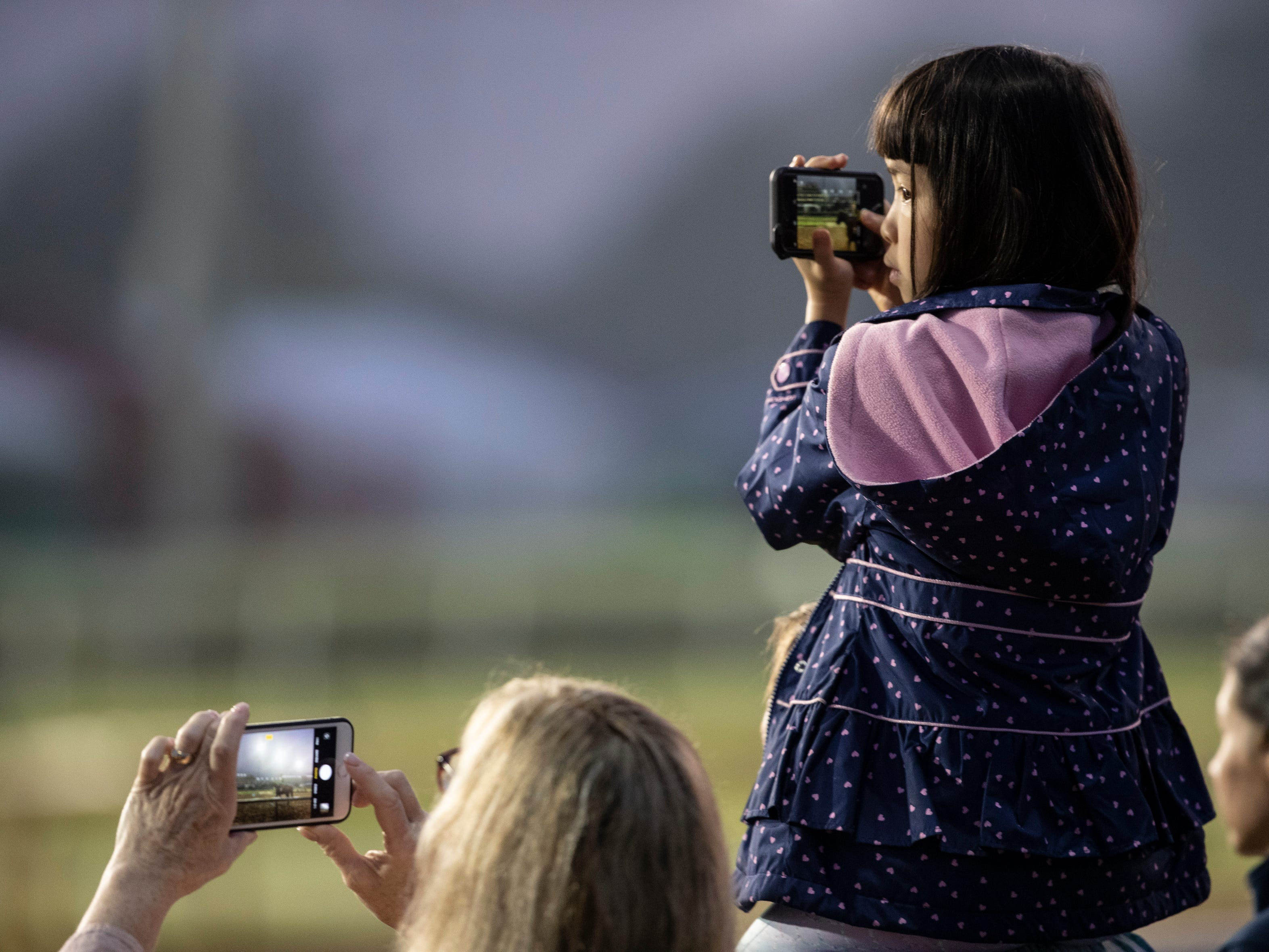 Mary Wilson left, and her daughter Isabel Wilson, 8, took photos of horses in training with their phones on the backside of Churchill Downs. The trip was a Christmas gift to Isabel's father, Chris. The Wilsons are from Virginia. May 2, 2019.