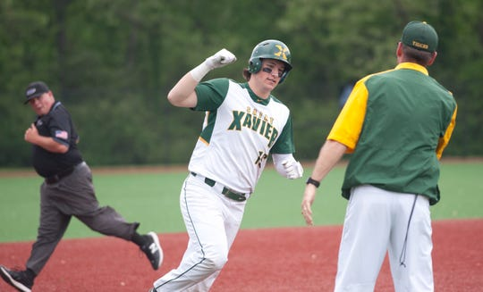 St. Xavier Ryan Nicholson rounds third base and heads for home after hitting the ball over the right field wall for a home run. He's about to slap hands with St. Xavier head coach Andy Porta.01 May 2019