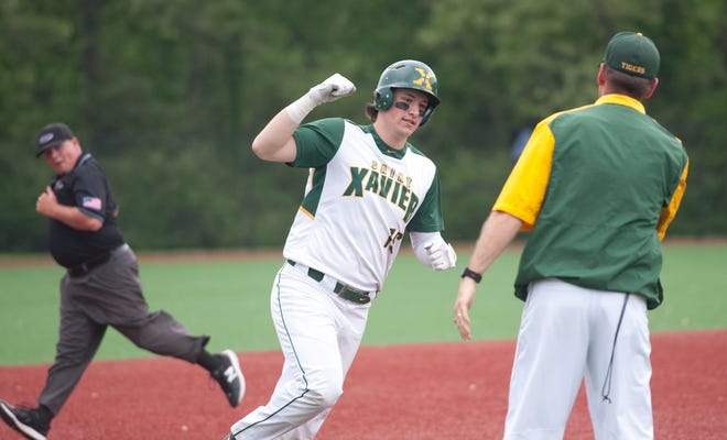 St. Xavier Ryan Nicholson rounds third base and heads for home after hitting the ball over the right field wall for a home run. He's about to slap hands with St. Xavier head coach Andy Porta.