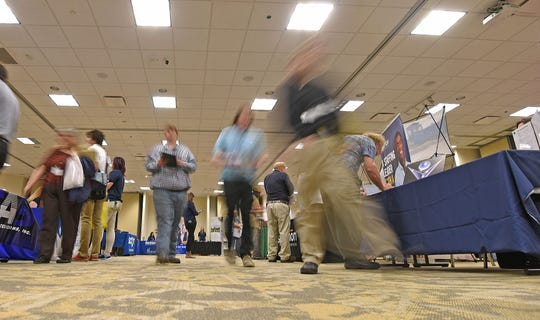 Job seekers searched the aisles Thursday during the job fair at the Mid-Ohio Conference Center.