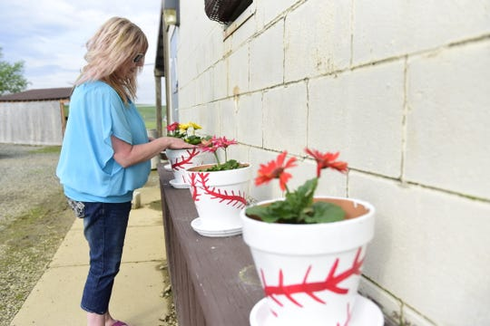 Jenni Yoder checks on a row of flowers she planted at the Field of Dreams baseball and softball complex in Mansfield.