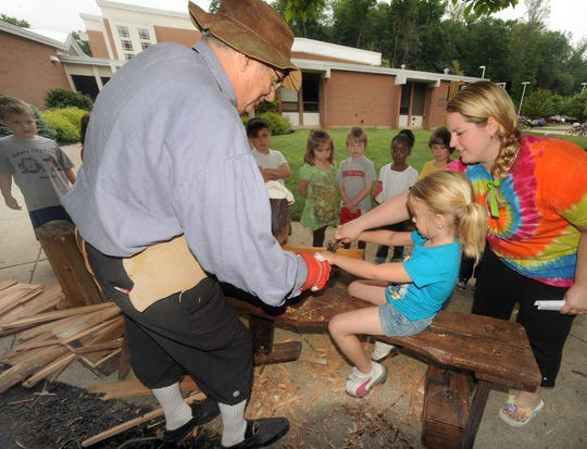 Retired WMRN Radio personality Charlie Evers, left, teaches kindergarten students from Benjamin Harrison Elementary School about the schnitzelbank, shaving bench, used to make wooden shingles in this file photo.