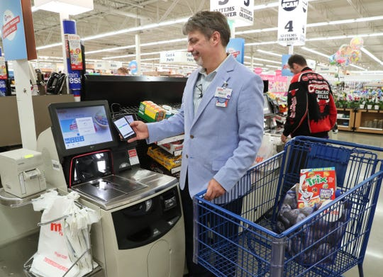 Mike Evert, store director of the Meijer in Kenosha, demonstrates how to check out with the app Thursday at the Greenfield store.