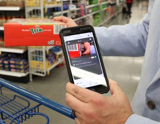 Mike Evert, store director of the Meijer in Kenosha, demonstrates the Shop & Scan feature in the Meijer app by scanning a box of cereal Thursday at the Greenfield store. The Kenosha store has been using the app in a pilot program for six months.  All Wisconsin stores will go live with it on Monday.
