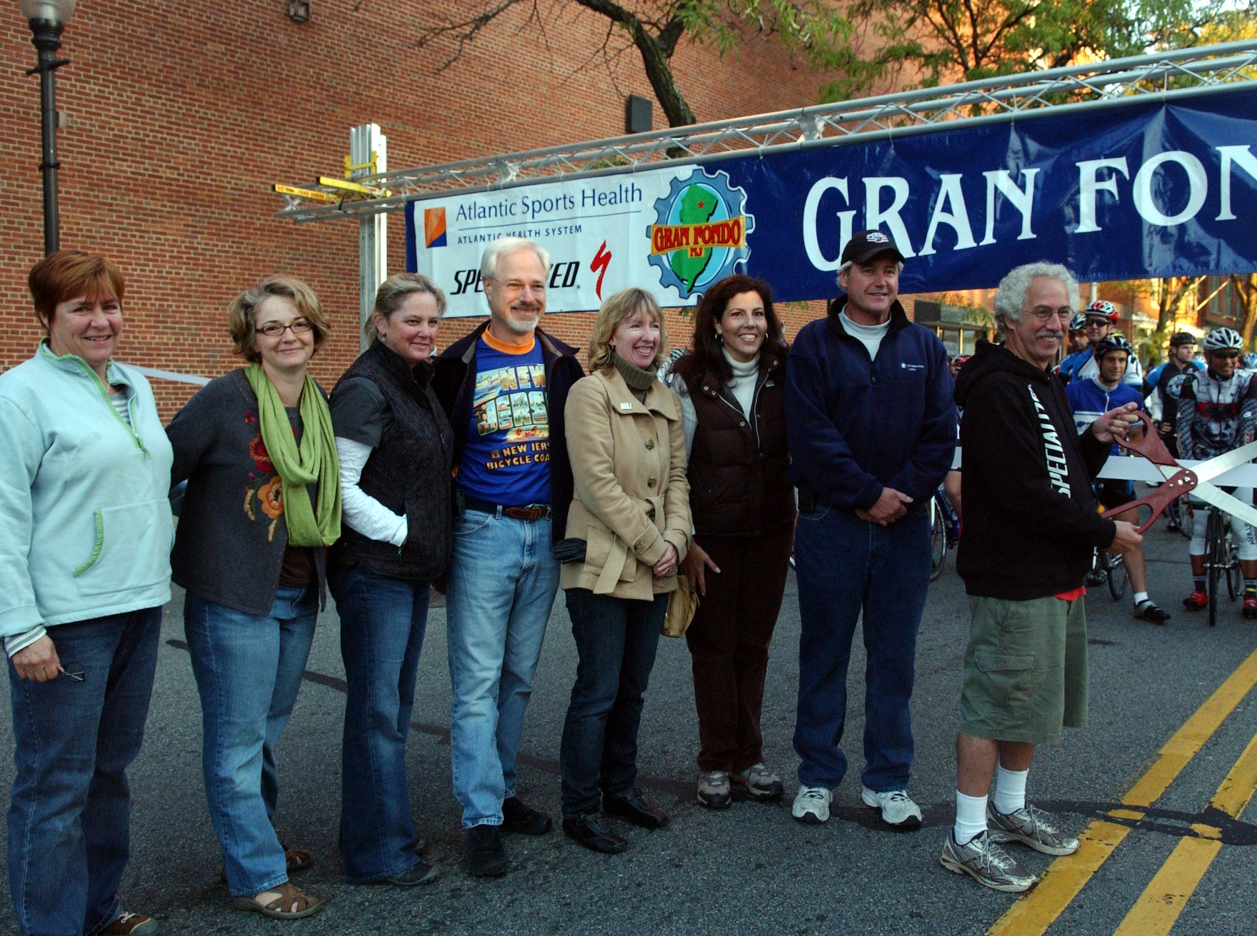 As ride organizer Marty Epstein holds the scissors, ride beneficiaries and dignitaries gather behind him (from right): Morristown Mayor Tim Dougherty, Wendi Zimmerman and Susan Robinson from Homeless Solutions, Morris Township Mayor H. Scott Rosenbush, and Grow It Green Morristown organizers Myra Bowie McCready, Samantha Rothman, Carolle Huber.