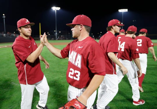 Alabama graduate closer Jeremy Randolph high-fives senior starter Sam Finnerty following a game against South Carolina on April 5, 2019 from Sewell-Thomas Stadium in Tuscaloosa. (Photo courtesy of Alabama athletics photography)