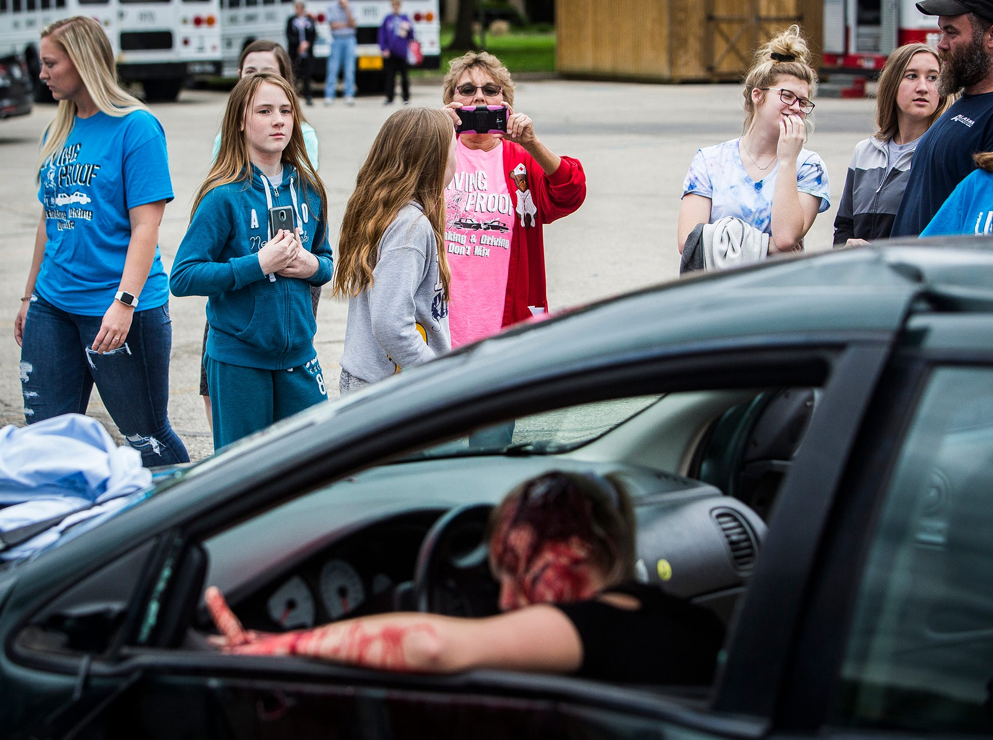 Attendees check out the fake blood and gore  during the 2019 Living Proof Crash Re-Enactment at Central Wednesday. The event seeks to raise awareness of the dangers of driving while intoxicated with re-enactments of crashes, court scenes and funerals. Makeup artist Brian Blair donated time and material for this year's Living Proof.
