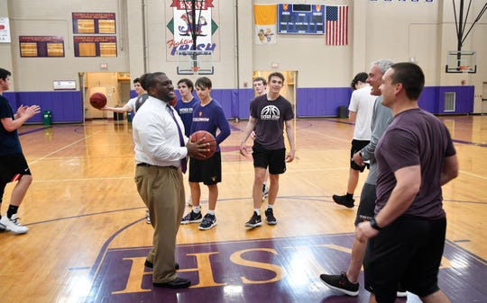 Father Ryan High School Athletic Director Dr. Devin DeLaughter -- the school's first African American administrator -- jokes with the basketball team during practice Wednesday, May 1, 2019, in Nashville, Tenn.