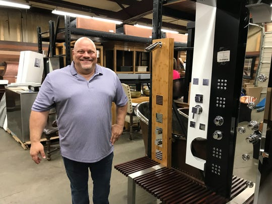 Mike Dunn, owner of Titan Treasures, shows off his warehouse store in Franklin.