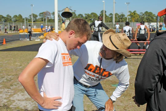 Mark McGarity, Lelytrack and field coach, consoles Tony Porter who wasn't pleased with his finish, at the Collier County Athletic Conference Track and Field Championships in 2013.