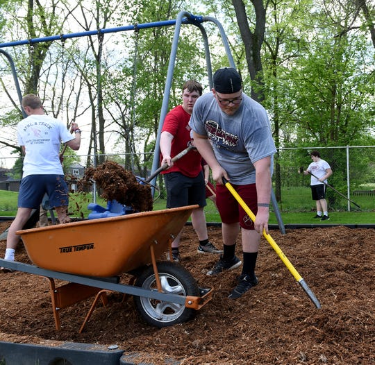 Newark High School football players sophomore Andrew LeFevre and junior Devin Nixon spread mulch at Hollander Pool during the high school's annual Community Cleanup Day. Wildcat student clubs and sports teams spent the day cleaning up and dispersing mulch in city parks as well as the school and surrounding neighborhood.