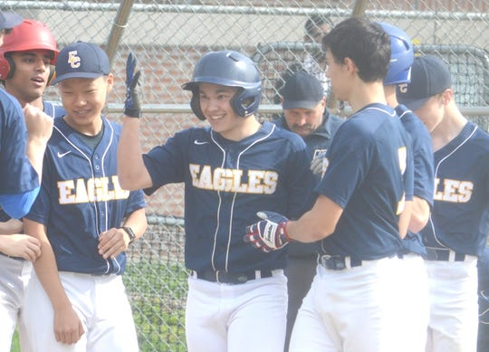 Eastern Christian senior Noah Troast (center) being congratulated by teammates after he smacked a two-run homer at Elmwood Park.