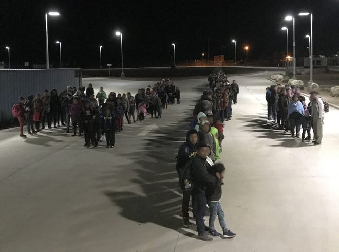 A large group of people cross the border at Antelope Wells, New Mexico.