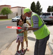 Gabriella Albillar, 7, along with her sister Sophia, 9, hands Stan Infante a birthday cake, Thursday May 2, 2019. Infante, who is a crossing guard at Valley View Elementary School, celebrated his 99th birthday April 25.