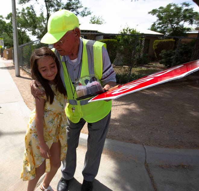 Stan Infante, a crossing guard at Valley View Elementary School, hugs Sophia Albillar, 9, who is in third grade at the school, who along with her sister Gabriella, 7, had just given him a cake, Thursday May 2, 2019. On April 25, Infante celebrated his 99th birthday.