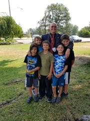 Gerry Washburn poses with his grandchildren. Washburn was hired to lead Carlsbad Municipal Schools as superintendent.