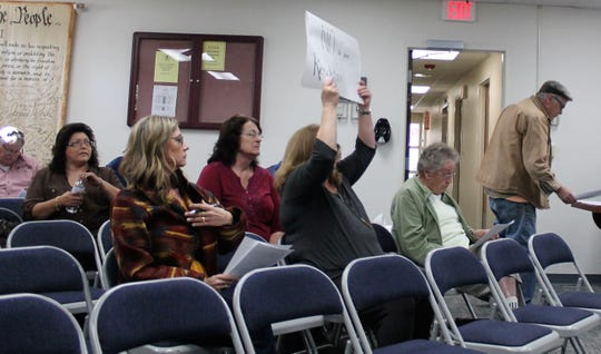 "Nadia Sikes holds up one side of her sign that says ""NO to this Resolution"" at the special Oteor County Commission meeting May 2."