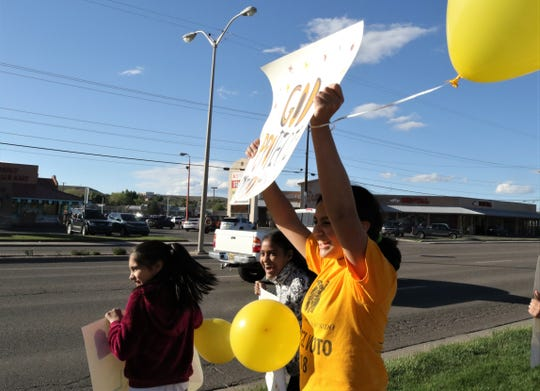 erenia Lopez holds a sign Wednesday during an International Workers Day rally in Farmington.