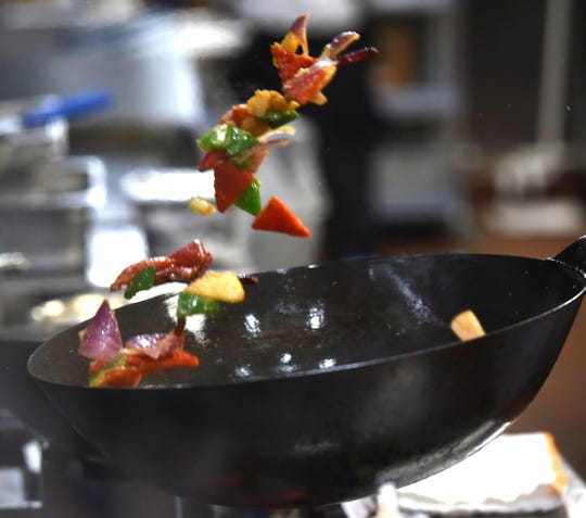 """A wok-ful of kung pao chicken is launched into the air by cook Shawn Linderman on May 2 at Zao Jun. Zao Jun is interpreted to mean """"kitchen god"""" in Chinese."""